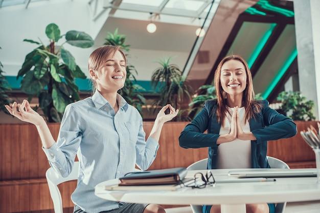2人の労働者女性がオフィスの机で瞑想します。