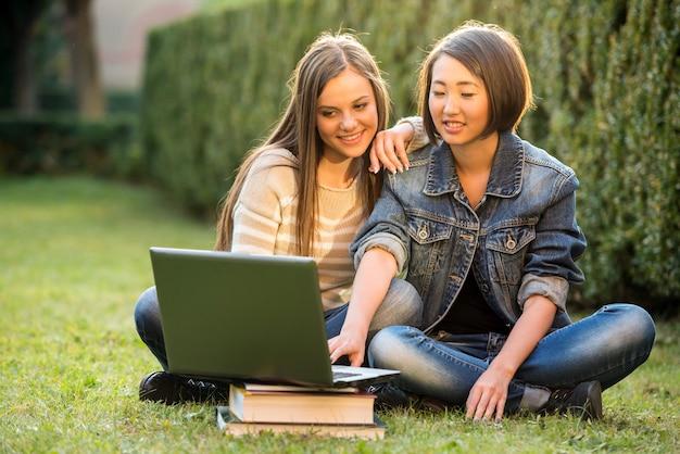 2人の笑顔の女子学生が芝生の上に座っています。