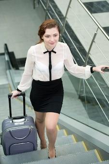スーツケースを持つ女性は2階に向かっています。