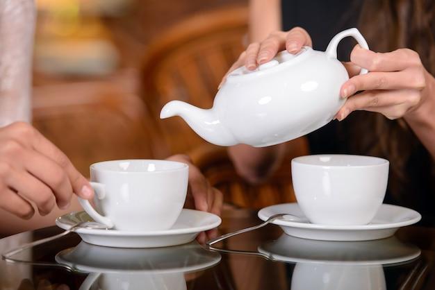 お茶を飲むと、カフェで話している2人の友人。