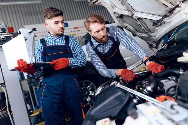 壊れた機械の上でガレージで働く2つの自動車整備士。