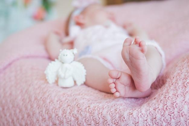 生まれたばかりの赤ちゃんの女の子のクローズアップ。赤ちゃんの足に焦点を当てます。ニットの面白い衣装を着て、寝ている2週齢の幼児の赤ちゃん