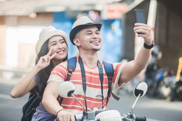 携帯電話のカメラを使用して自分撮りを取る2人の若いバックパッカー