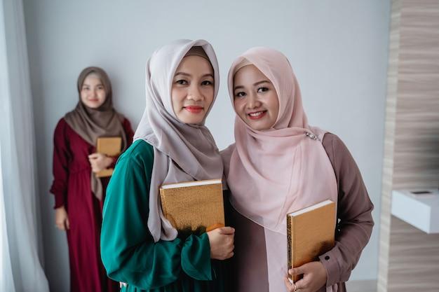 笑みを浮かべて2人のヒジャーブ女性はアルコーランの神聖な本を保持します