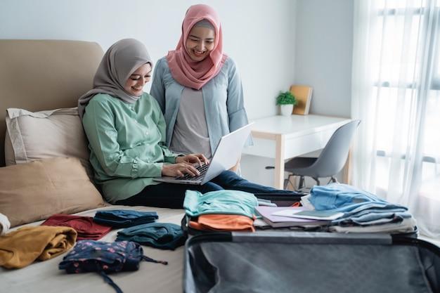 完全なスーツケースとラップトップを使用して2つのイスラム教徒の女性