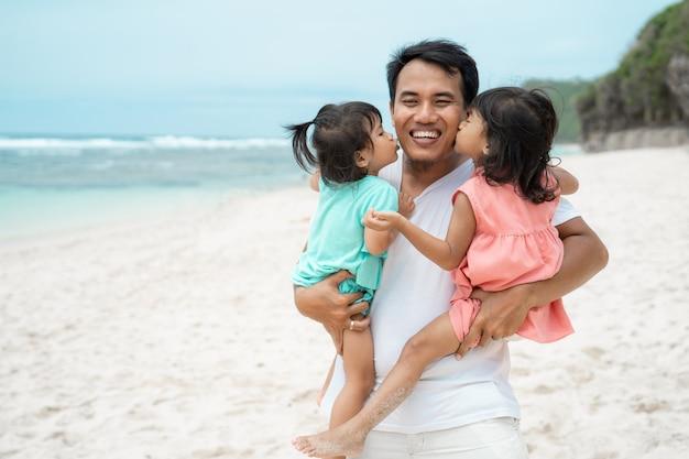 父親が2人の娘をビーチで運ぶ肖像画