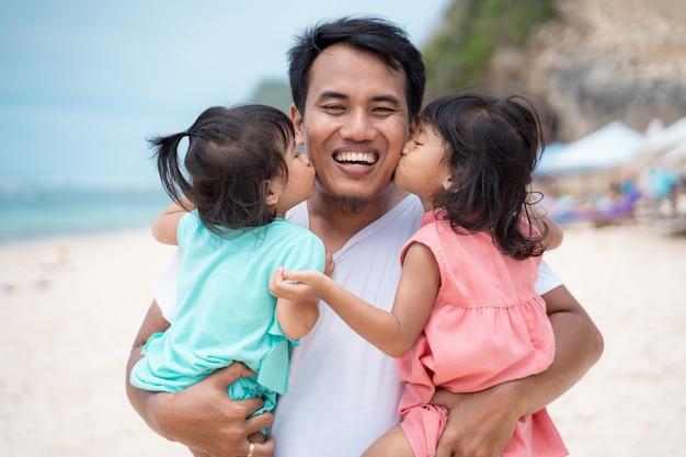 ビーチで彼の父親に一緒にキスする2つの小さな女の子