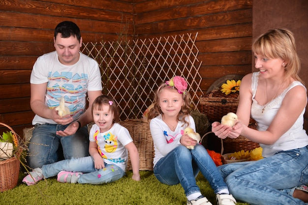 お父さん、お母さんと2人の美しい女の子が鶏と一緒にスタジオで写真を撮る