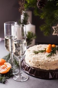 お祝いの新年のテーブル、ケーキ、みかん、シャンパン、グラス2杯