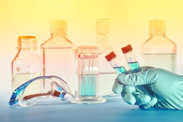 女性科学者の手にあるプラスチック製バイアルに入った2つの液体サンプル