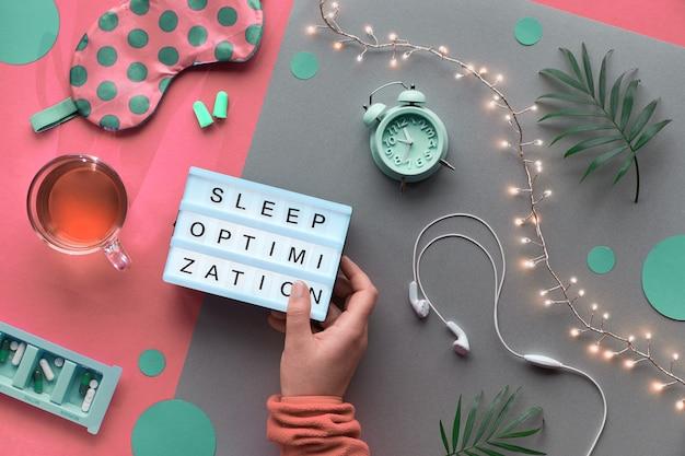 健康的な夜の睡眠の創造的なコンセプト。睡眠マスク、目覚まし時計、イヤホン、耳栓、お茶、錠剤。ライトで2トーンピンククラフト紙を分割します。テキスト「スリープ最適化を手に。