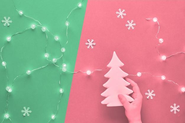 冬の休日のお祝い組成、2つのトーン、ピンクとネオミントグリーンのトーンのモノクロ画像。セラミックのモミの木の装飾を持っている手。新年やクリスマスフラットは、雪の結晶で横たわっていた。