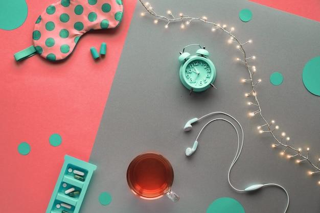 Здоровый ночной сон творческая концепция. спящая маска, будильник, наушники, беруши, чай и таблетки. разделите предпосылку бумаги ремесла цвета коралла 2 тонов с светлой гирляндой. копия-место, место для текста.