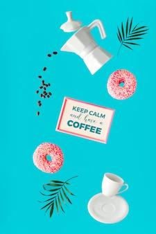 浮上シュルレアリスムのイメージ、コーヒー、手に2つのピンクのドーナツ。空飛ぶコーヒー豆。セラミックコーヒーメーカーとエスプレッソカップ。活気に満ちたトレンディな大胆な緑のミント色の背景にヤシの葉。