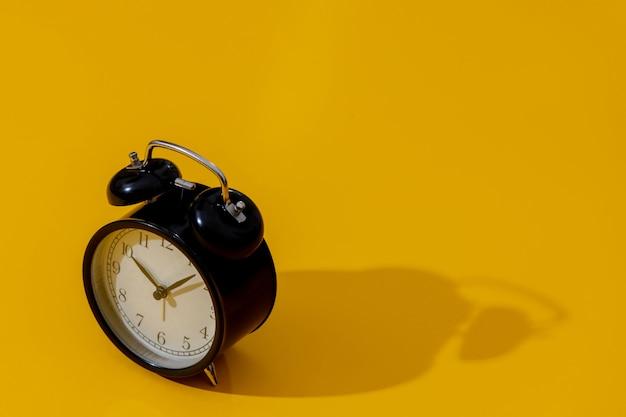 黄色の背景に2つの鐘の目覚まし時計
