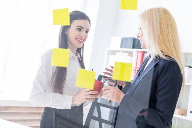 オフィスで話している2人の女の子。女の子は、ステッカーが貼られた透明なボードの近くの対話です。