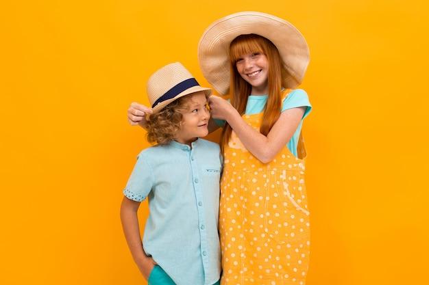 オレンジ色の2人の美しい子供がハグスタンド