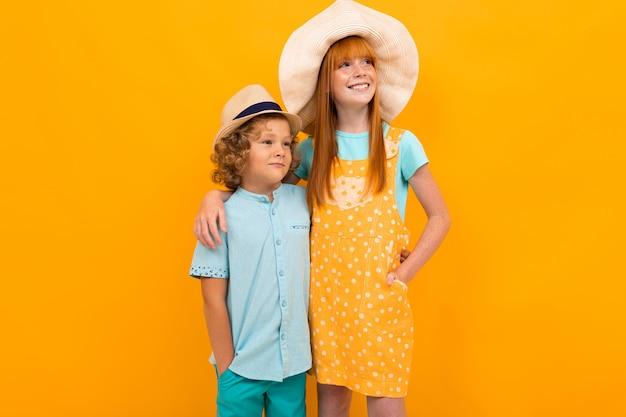 スタジオで夏の帽子の2人の赤い髪の子供