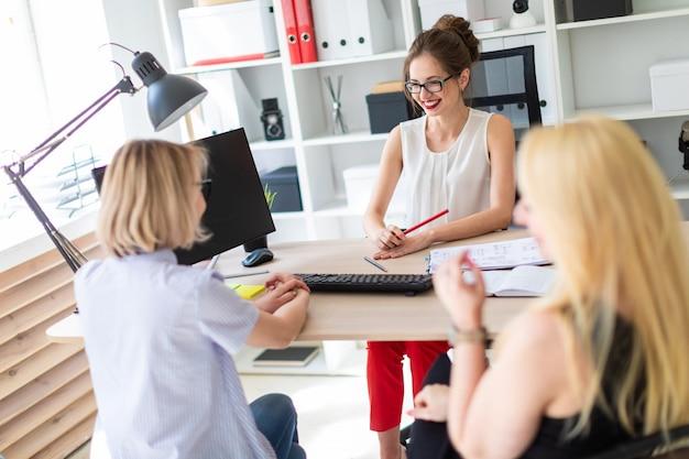 若い女の子が彼女のオフィスのテーブルに座っていて、2人の共同パートナーと話しています。