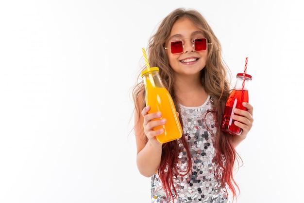 2つのアルコールフリードリンクを保持している陽気なブルネットの少女の笑顔