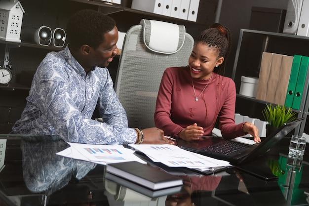 2人の笑う若い黒人は、オフィスの机に座って彼らのビジネスを議論する楽しい時を過す