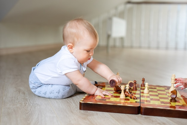 2人の赤ちゃん男の子と女の子が自宅の白い木の床でチェスをしています。