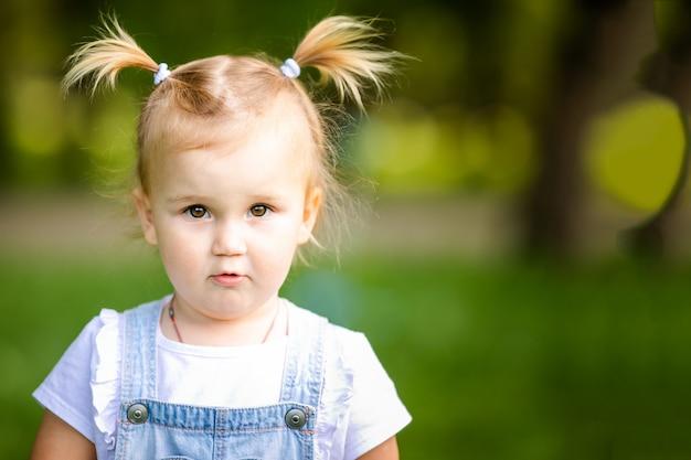 2つの小さなお下げと幸せな面白いブロンドの赤ちゃん女の子
