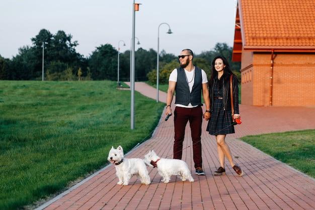 2つの白いそばきと一緒に公園でデートに愛のカップル