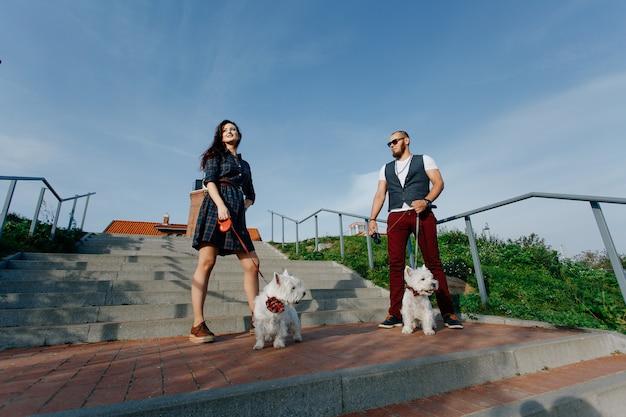 夫と妻の2つの白い小さな犬を歩く
