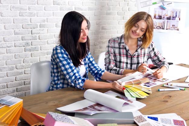 若いフリーランスのインテリアデザイナーがデザインスタジオで新しいアパートプロジェクトを開発しています。 2人の女性の女の子女性会議会議デスクでピンのスケッチの図面と新しいプロジェクトの下書き