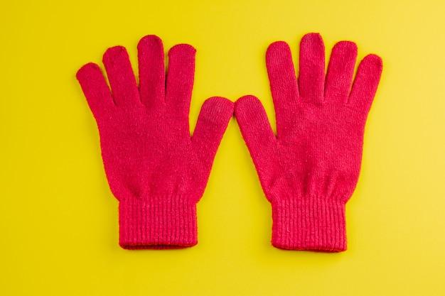 黄色に分離された2つの赤い手袋