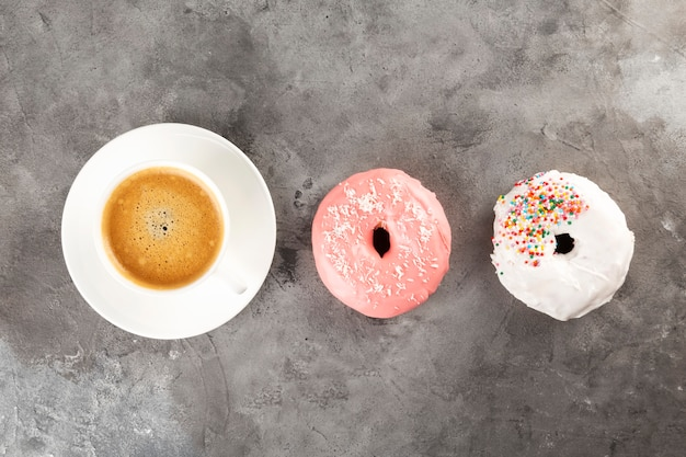 白い一杯のコーヒーと灰色の背景に白とピンクのアイシングで2つのドーナツ。フラットレイ