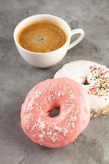 白いコーヒーのカップと灰色の背景に白とピンクのアイシングで2つのドーナツ