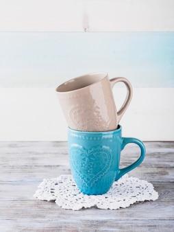 木製の背景にハートを持つ2つのセラミックカップ