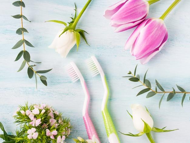 花のハーブと2つのパステル歯ブラシ