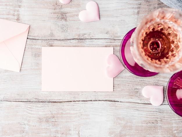 木製の織り目加工の背景にあなたのテキストを埋めるためにピンクの心空白の紙メモカードを持つ2つの茎シャンパングラス。