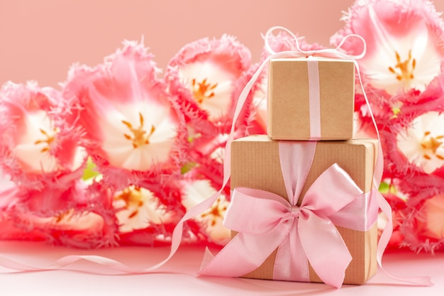クラフト紙とピンクの花の背景にピンクの弓で包まれた2つのギフトボックス。