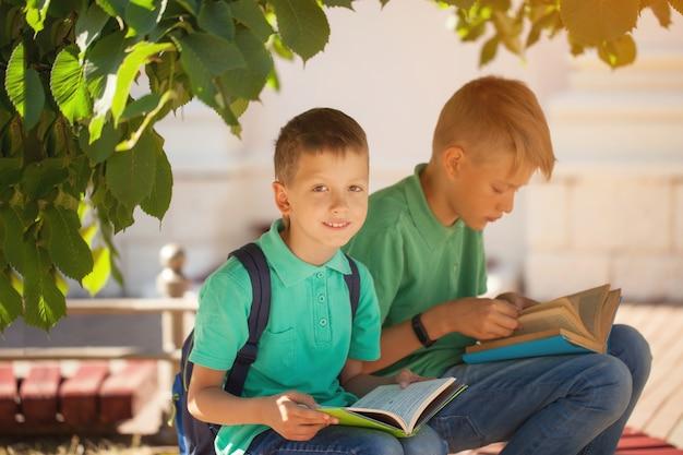 2つの学校の子供たちが木の下に座って、暖かい秋の日に本を読む