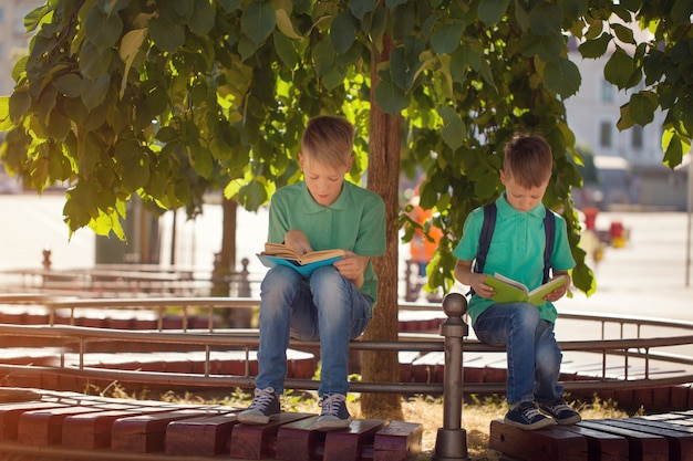 2つの学校の子供たちは木の下に座っていると日当たりの良い夏の日に本を読む