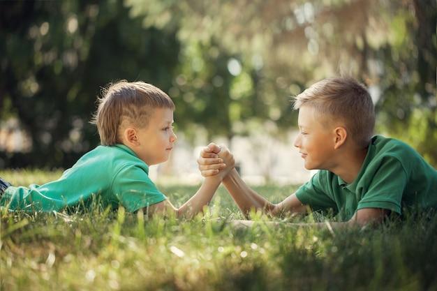 夏に緑の芝生で腕相撲に従事している2人の少年の手を握りしめ