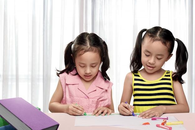 カラフルなクレヨンでお絵かき2つのアジアの女の子