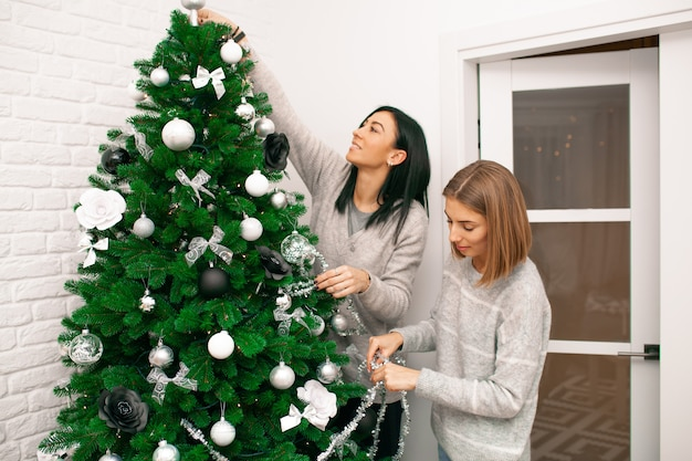 新年のお祝いに備えて、2人の若い女性がクリスマスツリーを飾ります。友人はクリスマスツリーを飾ります。クリスマス休暇中に美しい女の子が笑顔で楽しんでいます。