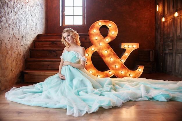 妊娠中の花嫁ブロンドは、母と妻になる準備をしています。女の子の体に長いターコイズ色のドレス。巻き毛と女性の顔の美しい笑顔。出生の2ヶ月前