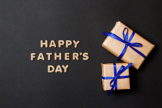 父の日を祝うグリーティングカード。黒い紙の背景に青いリボンと2つの工芸品の贈り物。