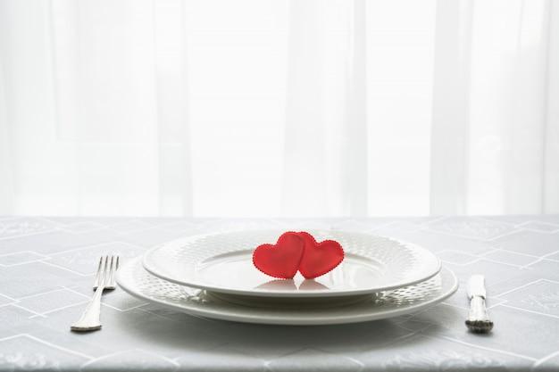 2つの心とバレンタインの日のテーブルの場所の設定。テキスト用のスペース日付への招待状。