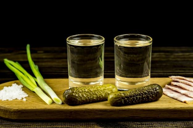ウォッカと2つのグラスとキュウリとベーコンと玉ねぎ