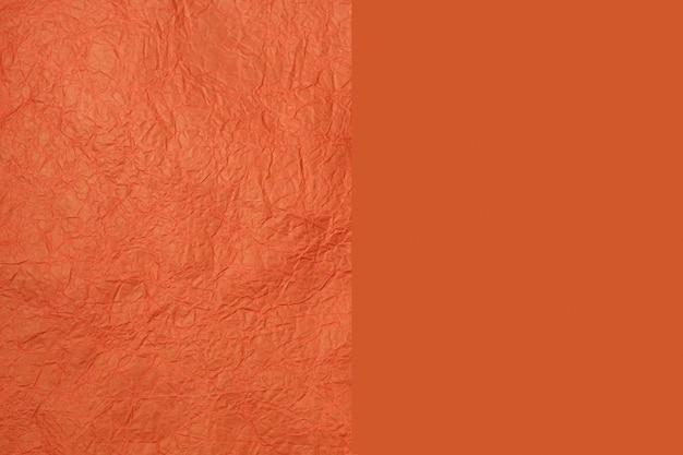 オレンジ色の2つの部分の紙のテクスチャ。しわのあるクレープオレンジ紙の構造。