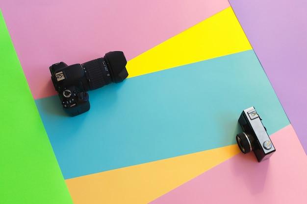 色付きの背景に2つのフィルムカメラをファッションします。