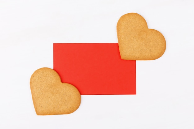 白地に2つのハート形のクッキーと赤いグリーティングカード。居心地の良い愛とバレンタインデーの背景とお祭りのコンセプトのシンボル