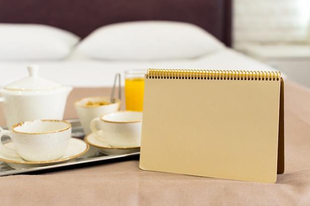 白いトレイ、白いベッド、朝食の概念上の2つの白いマグカップ